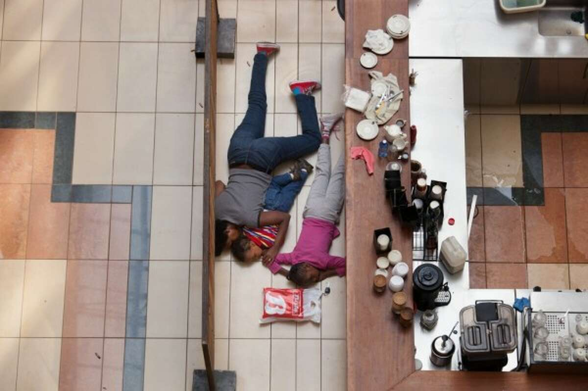 Nairobi, Kenya. Saturday, Sept. 21, 2013: A woman and children hide in the Westgate Mall. They escaped unharmed. (Photo: Tyler Hicks/The New York Times)