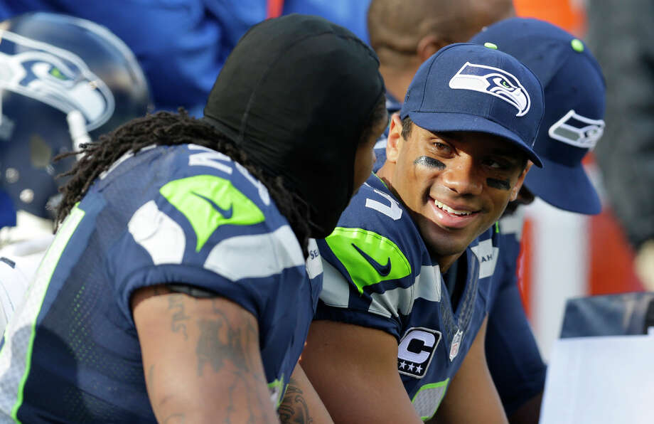 Seattle Seahawks quarterback Russell Wilson, right, smiles as he sits on the sidelines against the Jacksonville Jaguars in the second half of an NFL football game, Sunday, Sept. 22, 2013, in Seattle. Photo: Ted S. Warren, AP / AP