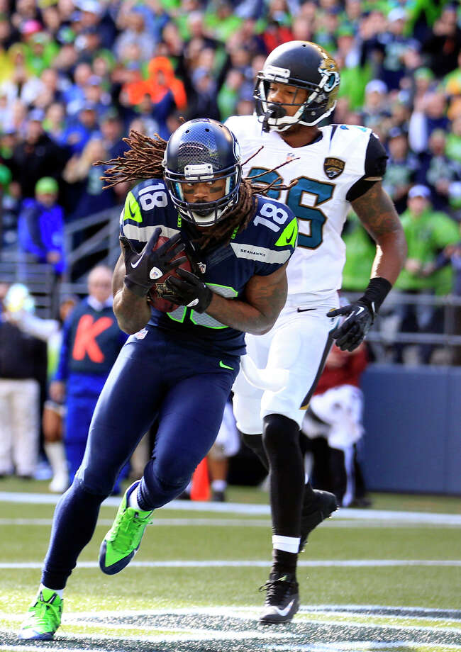 Seattle Seahawks' Sidney Rice (18) scores as Jacksonville Jaguars' Josh Evans pursues in the first half of an NFL football game on Sunday, Sept. 22, 2013, in Seattle. Photo: Stephen Brashear, AP / FR159797 AP