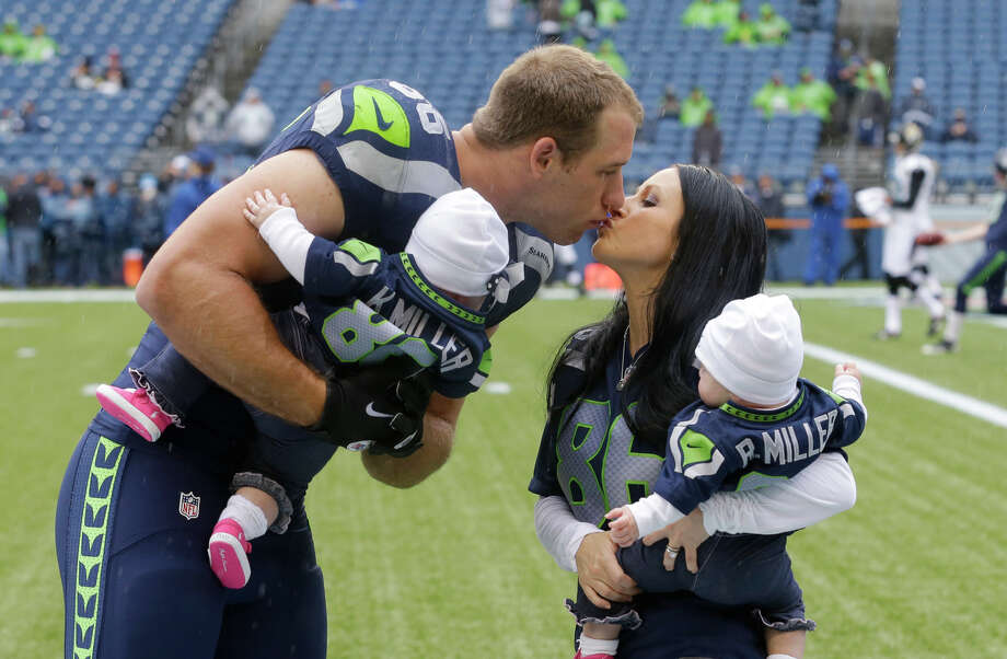Seattle Seahawks' Zach Miller, left, kisses his wife Ashley as they hold their seven-month old twins Remi and Kaydence after posing for photos before an NFL football game against the Jacksonville Jaguars, Sunday, Sept. 22, 2013, in Seattle. Photo: Ted S. Warren, AP / AP