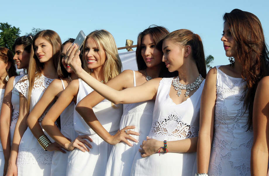 Miss World contestants, miss Kazakhstan Ainura Toleuova, second from right, poses with miss Kyrgyzstan Zhibek Nukeeva, third from right, as she takes photos with her mobile phone camera during the International World Peace Day celebrations at a park in Denpasar, Bali, Indonesia on Saturday, Sept. 21, 2013. The Miss World pageant final will be held in Bali on Sept. 28. Photo: Firdia Lisnawati, AP / AP