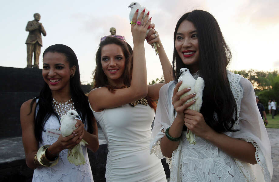 Miss World 2012 Yu Wenxia  of China, right, Miss Macedonia Fyro Kristina Spasenoska, center, and Miss Trinidad and Tobago Sherrece Villafana, left, hold doves during the International World Peace Day celebrations at a park in Denpasar, Bali, Indonesia on Saturday, Sept. 21, 2013. The Miss World pageant final will be held in Bali on Sept. 28. Photo: Firdia Lisnawati, AP / AP