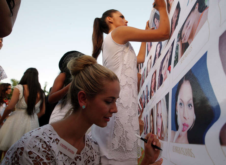 Miss World contestant, Miss United States Olivia Jordan, left, signed autograph on her photo during the International World Peace Day celebrations at a park in Denpasar, Bali, Indonesia on Saturday, Sept. 21, 2013. The Miss World pageant final will be held in Bali on Sept. 28. Photo: Firdia Lisnawati, AP / AP