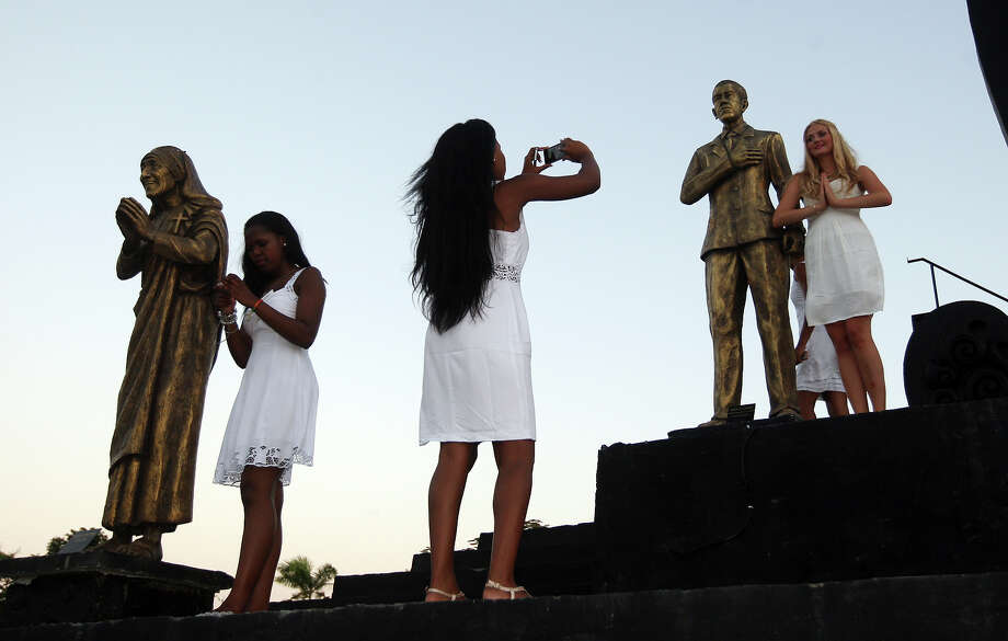 Miss World contestants, Miss Lesotho Mamahlape Matsoso , left, checks her picture as Miss Iceland Sigridur Dagbjort Asgeirsdottir, right, poses with a statue of the U.S. President Barack Obama  for photos during the International World Peace Day celebrations at a park in Denpasar, Bali, Indonesia on Saturday, Sept. 21, 2013. The Miss World pageant final will be held Sept. 28 in Bali. At center is unidentified contestant. Photo: Firdia Lisnawati, AP / AP