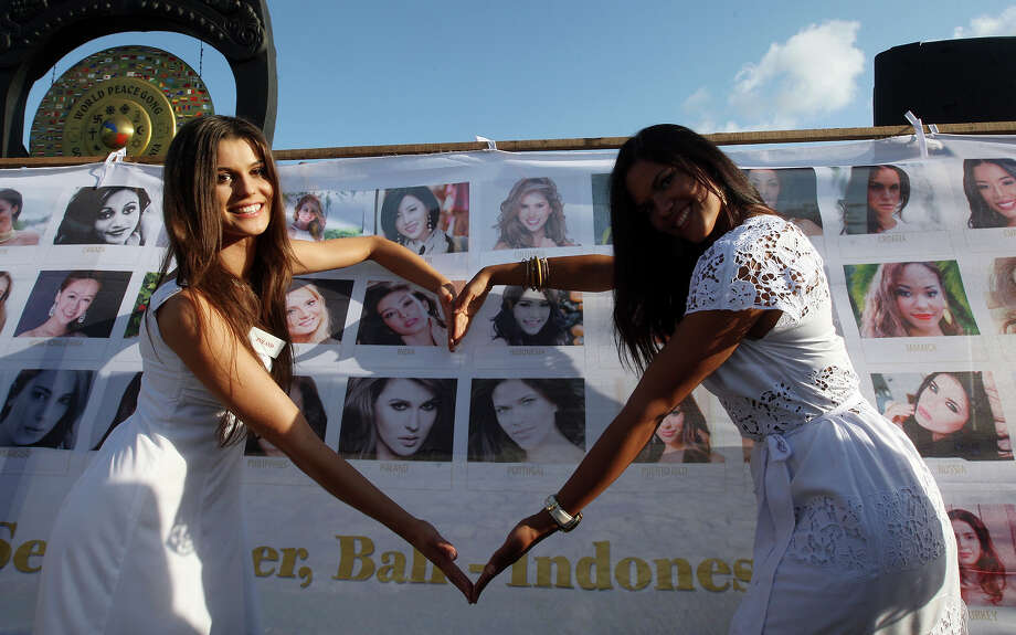 Miss World contestants, Miss Poland Katarzyna Krzeszowska, left, and Miss Portugal Elisabete Rodrigues, right, form a heart with arms as they pose for photos during the International World Peace Day celebrations at a park in Denpasar, Bali, Indonesia on Saturday, Sept. 21, 2013. The Miss World pageant final will be held in Bali on Sept. 28. Photo: Firdia Lisnawati, AP / AP