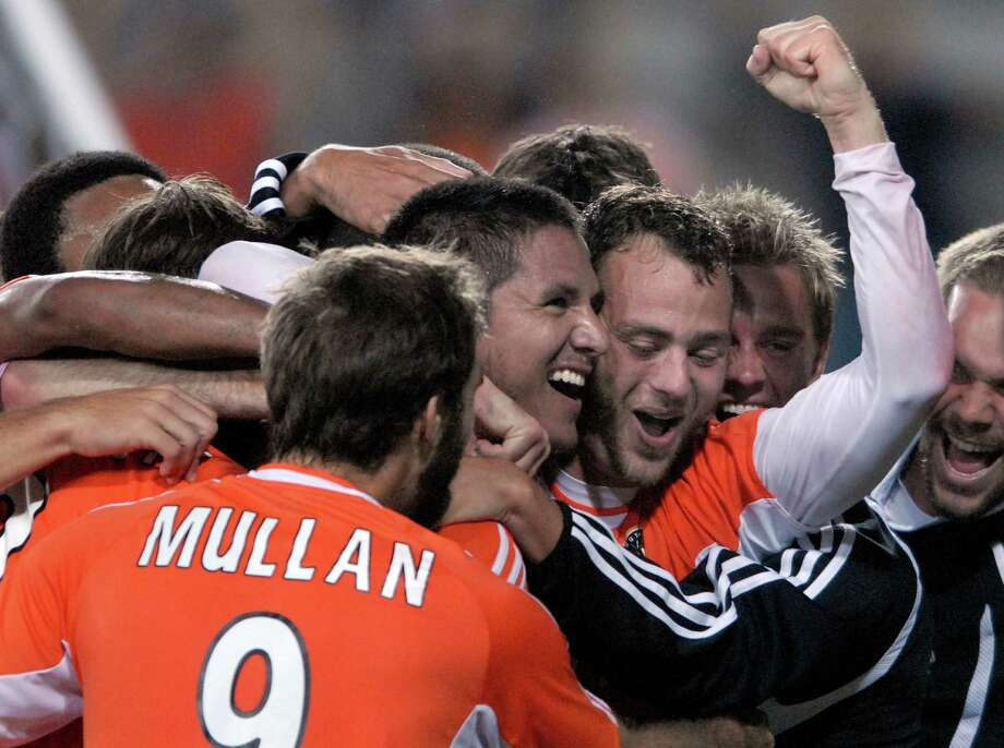 Houston Dynamo's Brad Davis gestures has he and the rest of the team hug Brian Ching center after he scored the winning goal against  Chivas USA's during the second half of a Major League Soccer playoff match Sunday, Oct. 29, 2006, in Houston.  Carlos Javier Sanchez : For The Chronicle Photo: Carlos Javier Sanchez, For The Chronicle / Freelance