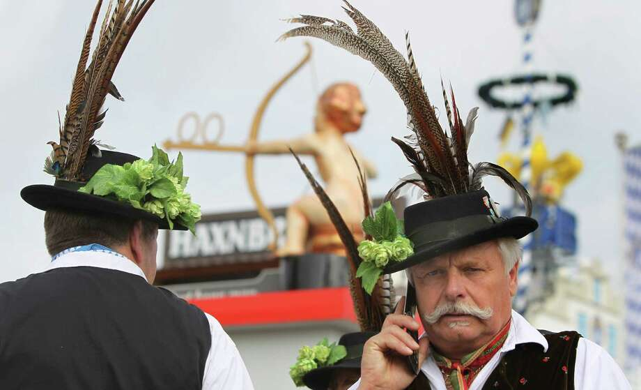 A man in traditional Bavarian clothes makes a phone call as he visits the Munich Oktoberfest beer festival in Munich, Germany  Saturday Sept. 21, 2013.   The world's largest beer festival,  lasts  from Sept. 21 to Oct. 6, 2013, and  is expected to attract more than six million guests from around the world. Photo: AP