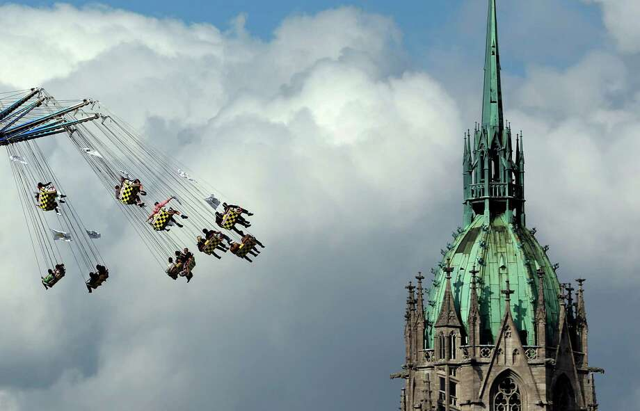 "People enjoy a swing ride in front of the St. Pauls church at the opening day of the Bavarian ""Oktoberfest"" beer festival in Munich, southern Germany, Saturday, Sept. 21, 2013. The world's largest beer festival, to be held from Sept. 21 to Oct. 6, 2013 will attract more than six million guests from around the world. Photo: AP"