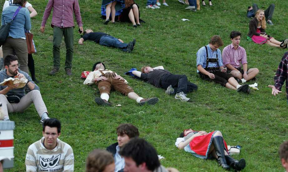 "Visitors rest on a meadow at the opening day of the 180th Bavarian ""Oktoberfest"" beer festival in Munich, southern Germany, Saturday, Sept. 21, 2013. The world's largest beer festival, to be held from Sept. 21 to Oct. 6, 2013 will attract more than six million guests from around the world. Photo: AP"