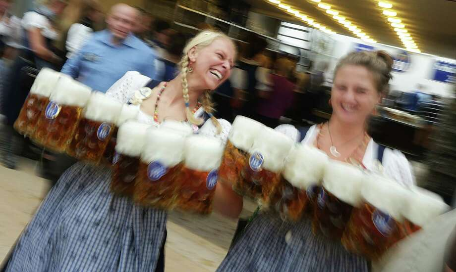 "Waitress carrie beer mugs during the opening ceremony in the ""Hofbraeuzelt' beer tent of the 180th Bavarian ""Oktoberfest"" beer festival in Munich, southern Germany, Saturday, Sept. 21, 2013. The world's largest beer festival, to be held from Sept. 21 to Oct. 6, 2013 will attract more than six million guests from around the world. Photo: AP"