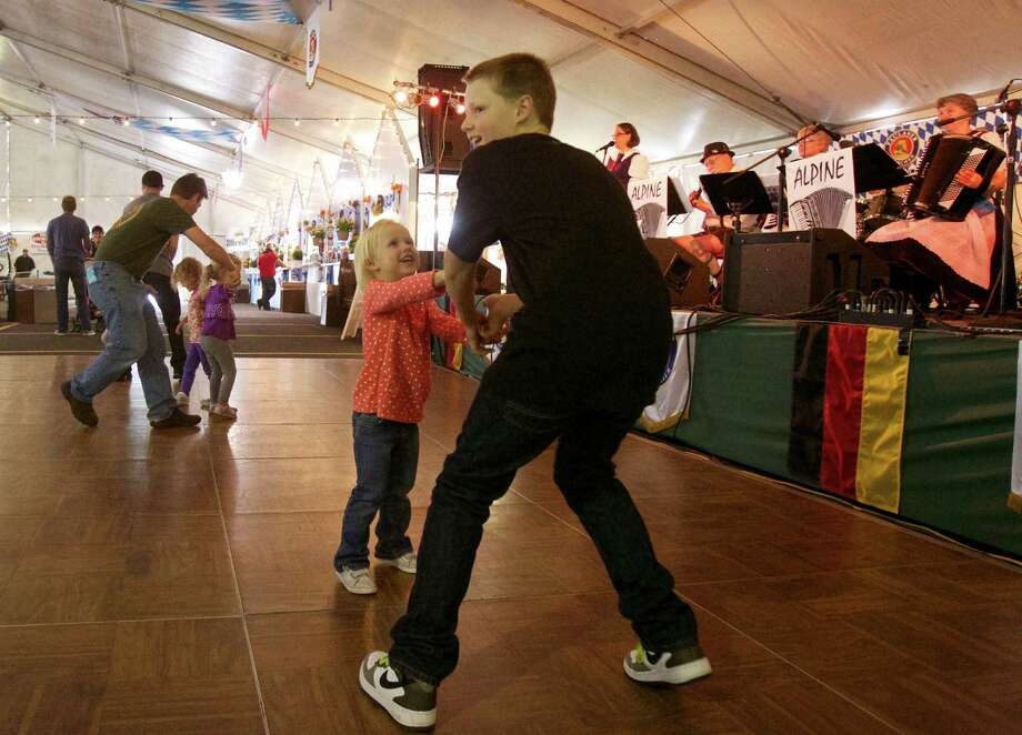 Caden Dunn, 12, dances the Chicken dance with his three-year-old sister, Catherine Dunn, in the big tent as Portlanders celebrate Oktoberfest at Oaks Park in Portland, Ore., Saturday Sept. 21, 2013. Photo: AP