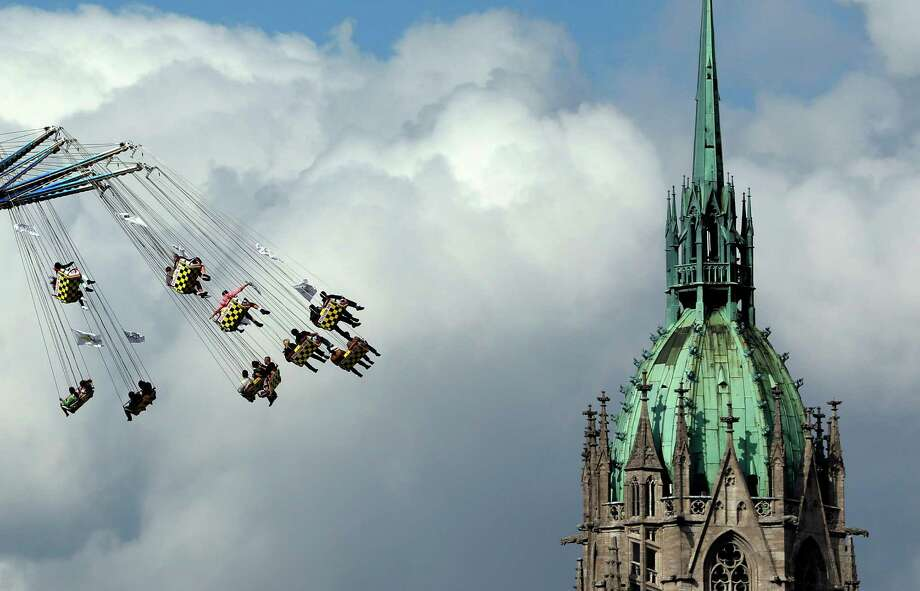People ride a swing in front of the St. Paul's church at the opening day of the Bavarian Oktoberfest beer festival in Munich on Saturday, Sept. 21, 2013. The world's largest beer festival, held Sept. 21-Oct. 6, is expected to attract more than six million guests from around the world. Photo: AP