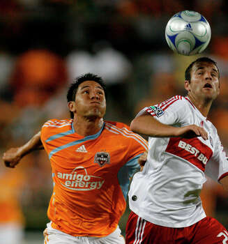 Houston Dynamo forward Brian Ching, left, and Chicago Fire defender Daniel Woolard battle for the ball in the second half of a Major League Soccer game between the Houston Dynamo and the Chicago Fire at Robertson Stadium on Sunday, Aug. 9, 2009, in Houston. The Dynamo, which gave up two early goals in the second half, came back and won the game 3-2 on a penalty shot goal by Stuart Holden in the 83rd minute. ( Julio Cortez / Chronicle ) Photo: Julio Cortez, Houston Chronicle / Houston Chronicle