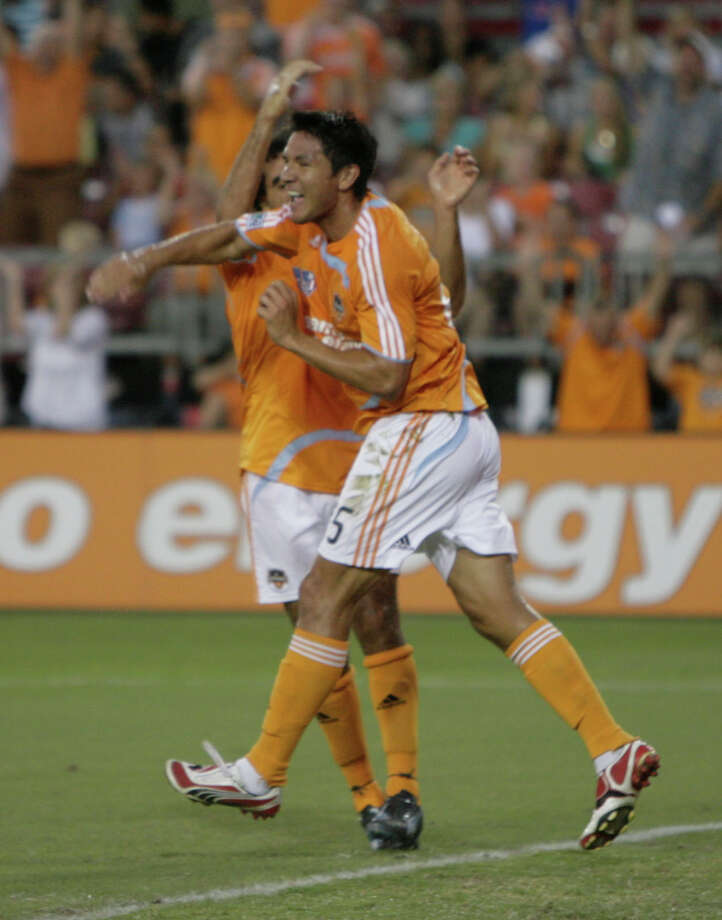 Houston Dynamo's Brian Ching, right, celebrates with teammate Dwayne De Rosario after Ching scored a goal against FC Dallas in the first half of a Major League Soccer game at Robertson Stadium on Thursday, June 26, 2008, in Houston. ( Julio Cortez / Chronicle ) Photo: Julio Cortez, Houston Chronicle / Houston Chronicle