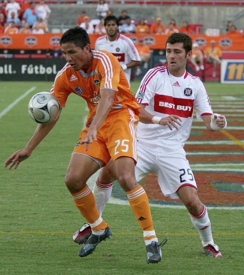 HOUSTON - AUGUST 31: Brian Ching #25 of the Houston Dynamo keeps the ball away from Gonzalo Segares #25 of the  Chicago Fire on August 31, 2008 at Robertson Stadium in Houston, Texas. Photo: Thomas B. Shea, MLS Via Getty Images / Getty Images