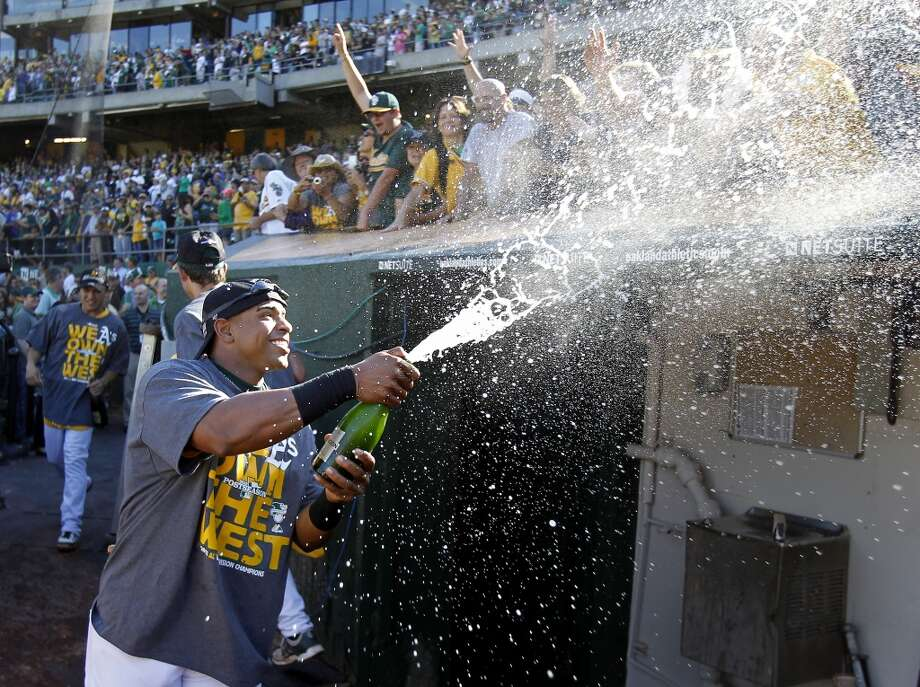 Outfielder Yoenis Cespedes sprayed the crowd with bubbly over the A's dugout after the game. The Oakland A's defeated the Twins 11-7 and captured the American League Western division championship Sunday September 22, 2013 at O.co coliseum in Oakland, Calif. Photo: Brant Ward, The Chronicle
