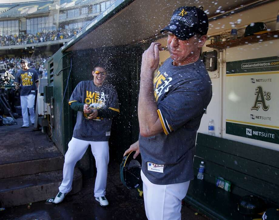 The A's Jarrod Parker (left) gave his manager Bob Melvin a champagne bath after the victory. The Oakland A's defeated the Twins 11-7 and captured the American League Western division championship Sunday September 22, 2013 at O.co coliseum in Oakland, Calif. Photo: Brant Ward, The Chronicle