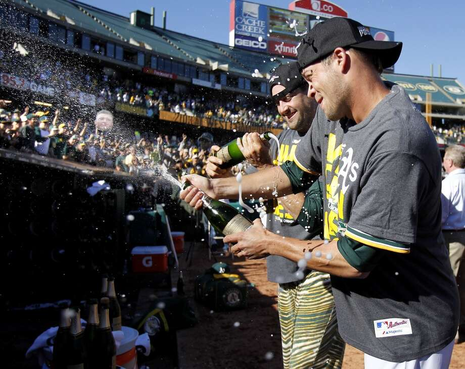 Pitcher Evan Scriber (right), who finished the win worked on a bottle of champagne after his inning. The Oakland A's defeated the Twins 11-7 and captured the American League Western division championship Sunday September 22, 2013 at O.co coliseum in Oakland, Calif. Photo: Brant Ward, The Chronicle