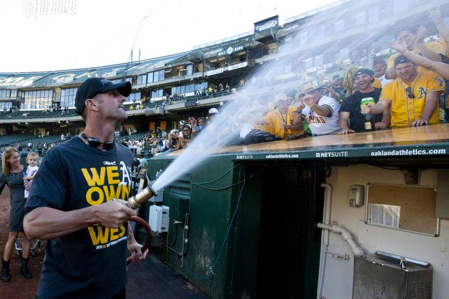 Grant Balfour sprays fans with a water hose after the game against the Minnesota Twins. Photo: Jason O. Watson, Getty Images