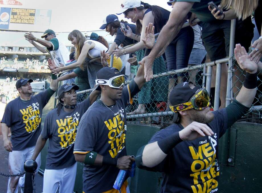 Oakland A's players, some donning goggles, thanked fans after the afternoon victory. The Oakland A's defeated the Twins 11-7 and captured the American League Western division championship Sunday September 22, 2013 at O.co coliseum in Oakland, Calif. Photo: Brant Ward, The Chronicle