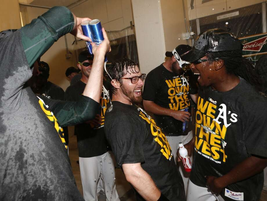 Oakland Athletics' Eric Sogard, center, celebrates with teammate Jemile Weeks, right, after defeating the Minnesota Twins in a baseball game to become American League West champions, Sunday, Sept. 22, 2013, in Oakland, Calif. Photo: Beck Diefenbach, Associated Press