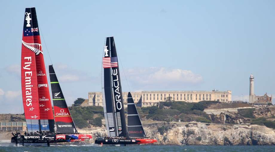 Oracle Team USA and Emirates Team New Zealand pass in front of Alcatraz Island during the America's Cup sailing event in San Francisco on Sunday, Sept. 22, 2013. Photo: Mathew Sumner, Special To The Chronicle