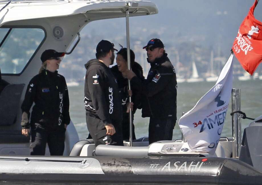Oracle Corporation CEO Larry Ellison, right, chats with people on his boat during the 15th race of the America's Cup sailing event between Oracle Team USA and Emirates Team New Zealand, Sunday, Sept. 22, 2013, in San Francisco. Oracle Team USA won both 14th and 15th races Sunday. Photo: George Nikitin, Associated Press
