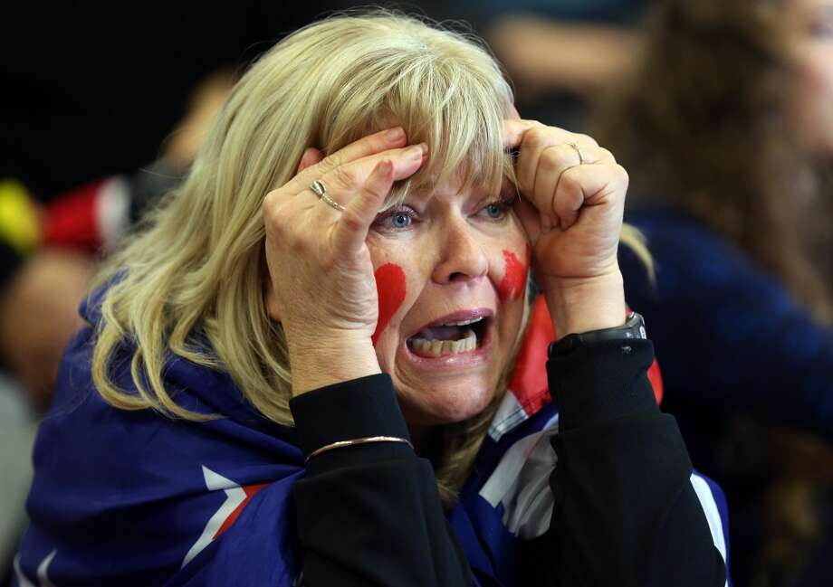 A sailing fan of Team New Zealand reacts while watching the racing in the America's Cup in San Francisco on large television screens set up at a venue in downtown Auckland on September 23, 2013. Oracle Team USA notched a pair of wins in the America's Cup on September 23, repeatedly denying the Kiwis the one victory they need to claim yachting's top prize. Photo: Michael Bradley, AFP/Getty Images