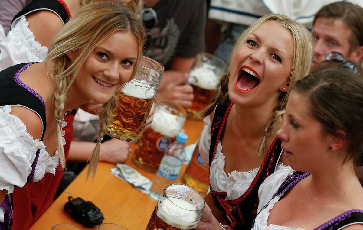"""Women celebrate the opening ceremony in the """"Hofbraeuzelt' beer tent of the 180th Bavarian """"Oktoberfest"""" beer festival in Munich, southern Germany, Saturday, Sept. 21, 2013. The world's largest beer festival, to be held from Sept. 21 to Oct. 6, 2013 will attract more than six million guests from around the world."""