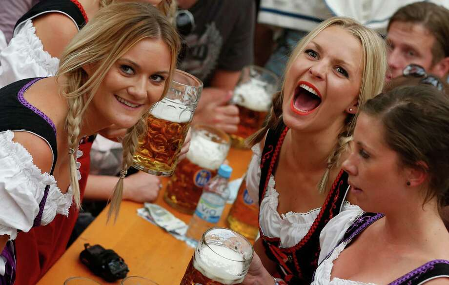"Women celebrate the opening ceremony in the ""Hofbraeuzelt' beer tent of the 180th Bavarian ""Oktoberfest"" beer festival in Munich, southern Germany, Saturday, Sept. 21, 2013. The world's largest beer festival, to be held from Sept. 21 to Oct. 6, 2013 will attract more than six million guests from around the world. Photo: AP"