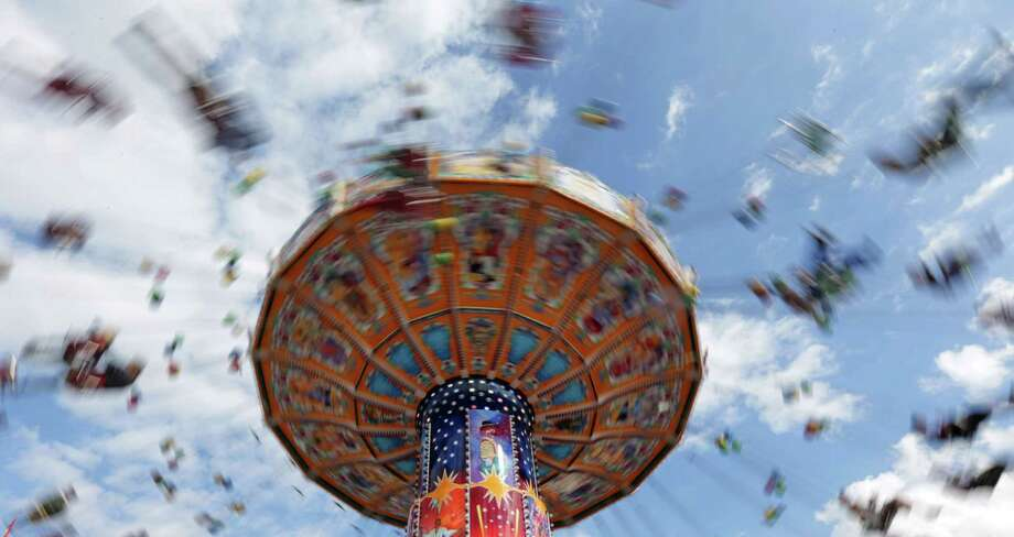 "People enjoy a fairground ride at the opening day of the 180th Bavarian ""Oktoberfest"" beer festival in Munich, southern Germany, Saturday, Sept. 21, 2013. The world's largest beer festival, to be held from Sept. 21 to Oct. 6, 2013 will attract more than six million guests from around the world. Photo: AP"