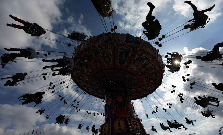 """People enjoy a swing ride  at the opening day of the 180th Bavarian """"Oktoberfest"""" beer festival in Munich, southern Germany, Saturday, Sept. 21, 2013. The world's largest beer festival, to be held from Sept. 21 to Oct. 6, 2013 will attract more than six million guests from around the world. Photo: AP"""