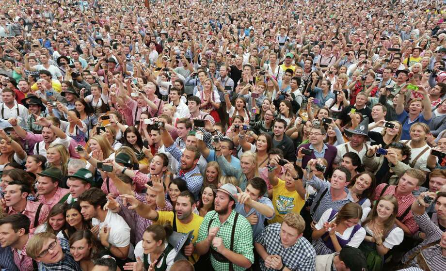 """Around 7,000 people await the start of the opening ceremony of the 180th Bavarian """"Oktoberfest"""" beer festival in Munich, southern Germany, Saturday, Sept. 21, 2013. The world's largest beer festival, to be held from Sept. 21 to Oct. 6, 2013 will attract more than six million guests from around the world. Photo: AP"""