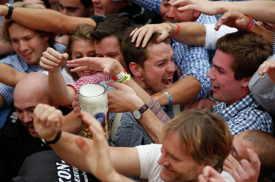 "Young people fight to get beer during the opening ceremony in the ""Hofbraeuzelt' beer tent of the 180th Bavarian ""Oktoberfest"" beer festival in Munich, southern Germany, Saturday, Sept. 21, 2013. The world's largest beer festival, to be held from Sept. 21 to Oct. 6, 2013 will attract more than six million guests from around the world. Photo: AP"