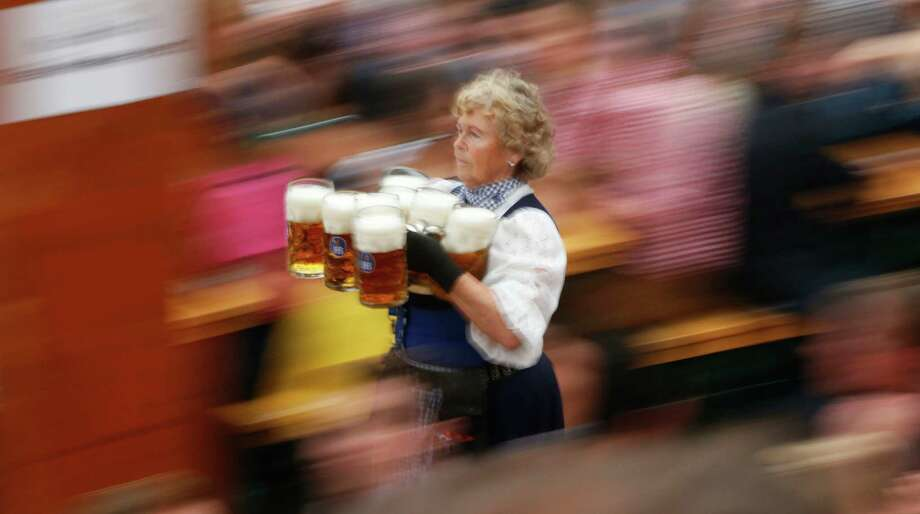 "A waitress carries beer mugs during the opening ceremony in the ""Hofbraeuzelt' beer tent of the 180th Bavarian ""Oktoberfest"" beer festival in Munich, southern Germany, Saturday, Sept. 21, 2013. The world's largest beer festival, to be held from Sept. 21 to Oct. 6, 2013 will attract more than six million guests from around the world. Photo: AP"