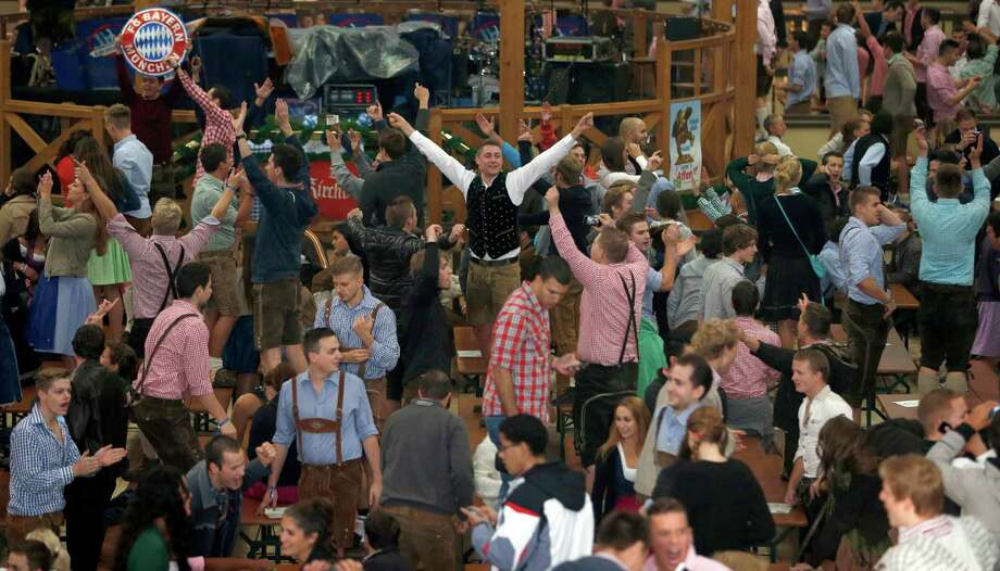 """People celebrate after entering a beer tent for the opening ceremony of the 180th Bavarian """"Oktoberfest"""" beer festival in Munich, southern Germany, Saturday, Sept. 21, 2013. The world's largest beer festival, to be held from Sept. 21 to Oct. 6, is expected to attract more than six million guests from around the world. Photo: AP"""