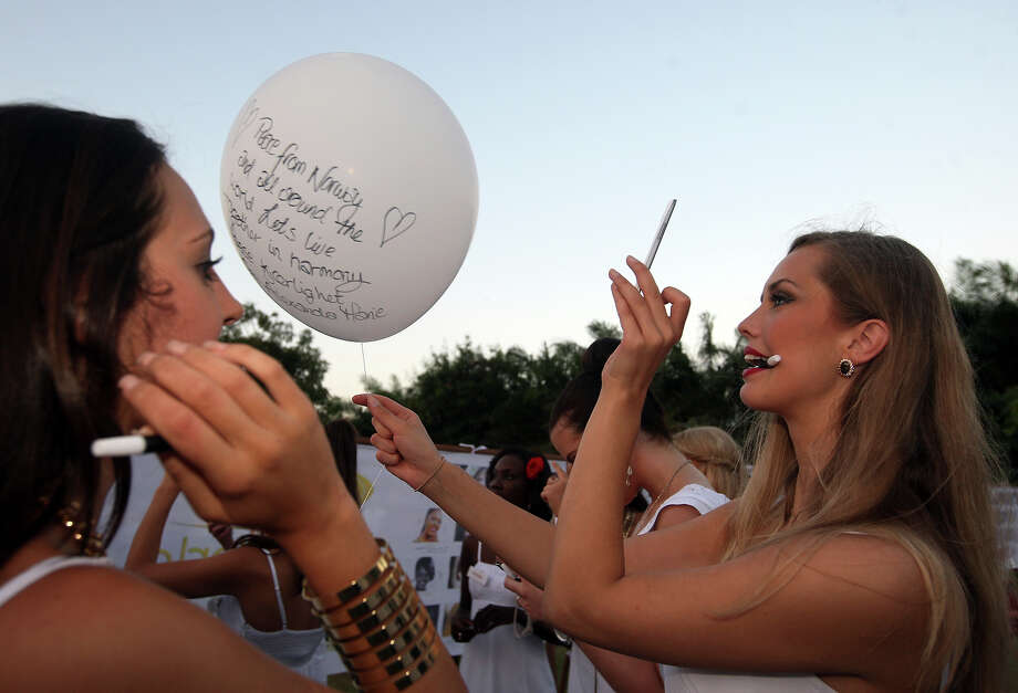 Miss World contestant, miss Norway Alexandra Marie Backstrom, right, take a photo of her message on a balloon with her mobile phone camera during the International World Peace Day celebrations at a park in Denpasar, Bali, Indonesia on Saturday, Sept. 21, 2013. The Miss World pageant final will be held in Bali on Sept. 28. Photo: Firdia Lisnawati, AP / AP