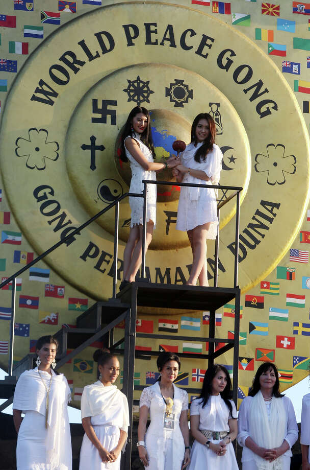 Miss World 2012 Wenxia Yu of China, top left, and Miss Indonesia Vania Larissa, top right, hit a giant world peace gong as other contestants pose for photos during the International World Peace Day celebrations at a park in Denpasar, Bali, Indonesia on Saturday, Sept. 21, 2013. The Miss World pageant is currently underway. Photo: Firdia Lisnawati, AP / AP