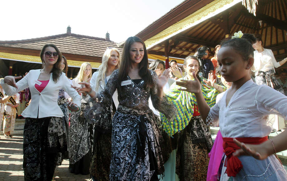 Miss World pageant contestant Miss Melinder Bhullar of Malaysia, front row center, and others, second row from left, Miss Pagmadulam Sukbaatar of Mongolia in a white jacket, Miss Erin Holland of Australia also in a white jacket, and Miss Penina Maree Paeu of Samoa, in a checkered green and yellow shawl, learn Balinese dance during their visit to a Hindu temple in Besakih, Bali, Indonesia Wednesday, Sept. 11, 2013. Photo: Firdia Lisnawati, ASSOCIATED PRESS / AP2013
