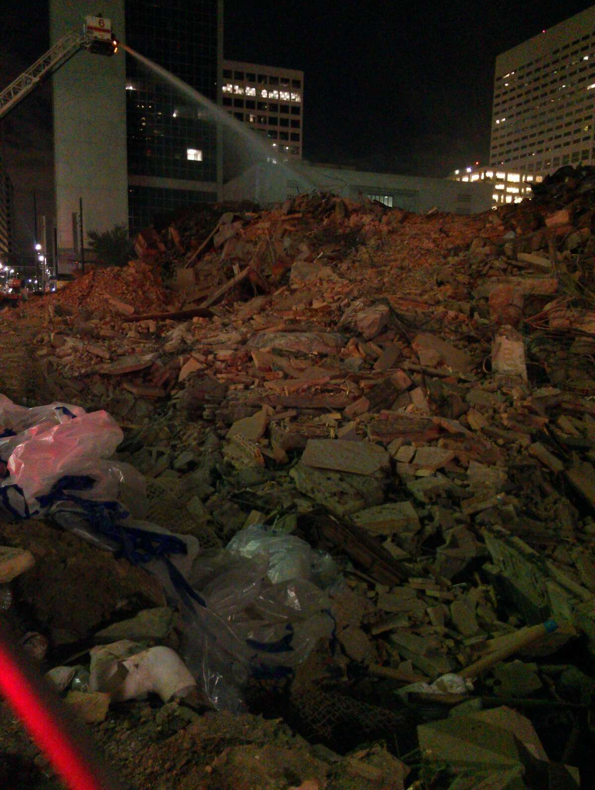 According to HFD, a small flash fire occurred inside the rubble late Sunday night, bringing out fire officials to soak the pile with water to tap it out. (Craig Hlavaty / Houston Chronicle)