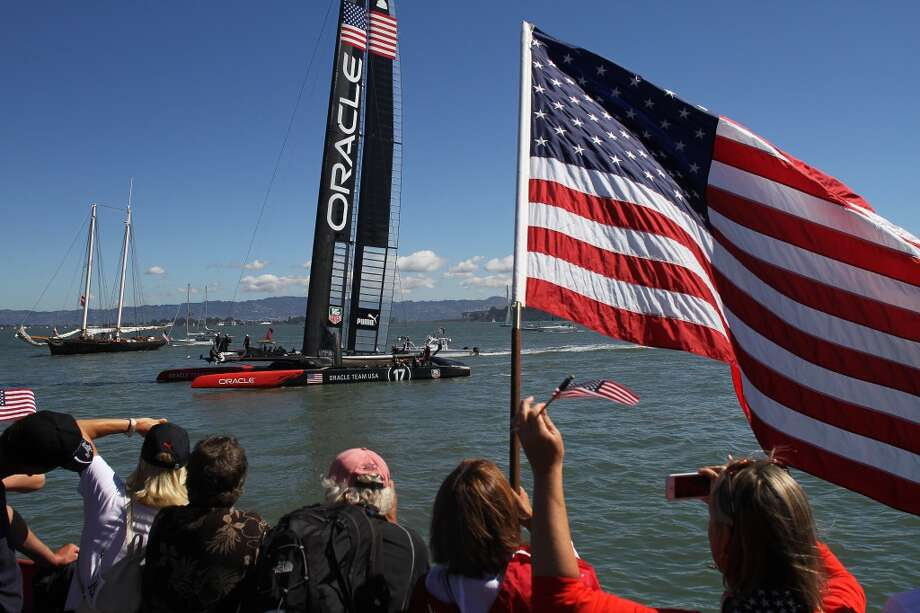 Spectators cheer and wave flags as Oracle Team USA passes by the America's Cup Pavilion on Sunday, Sept. 22, 2013. Fans gathered at the America's Cup Pavilion in the Embarcadero to watch Oracle Team USA go head-to-head with Emirates Team New Zealand in Races 14 and 15. Photo: James Tensuan, SFC