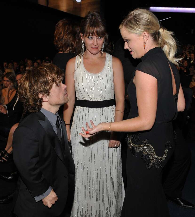 Peter Dinklage, Erica Schmidt and Amy Poehler  in the audience at the 65th Primetime Emmy Awards at Nokia Theatre on Sunday Sept. 22, 2013, in Los Angeles.  (Photo by John Shearer/Invision for Academy of Television Arts & Sciences/AP Images)