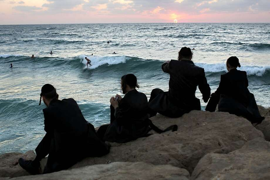 Sukkot surfing: Ultra-Orthodox Jewish men watch Israeli surfers during the Jewish holiday of Sukkot in the southern Israeli port city of Ashdod. Photo: Oded Balilty, Associated Press