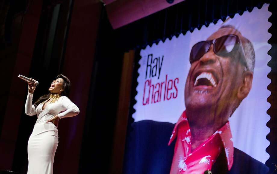 "Ray Charles has officially made it: A stamp featuring musician Ray Charles is unveiled as singer Ashanti performs at the event at Morehouse College in Atlanta, Monday, Sept. 23, 2013. The U.S. Postal Service is planning to add soul singer Ray Charles to its ""Music Icons Forever"" stamp series. Photo: David Goldman, Associated Press"