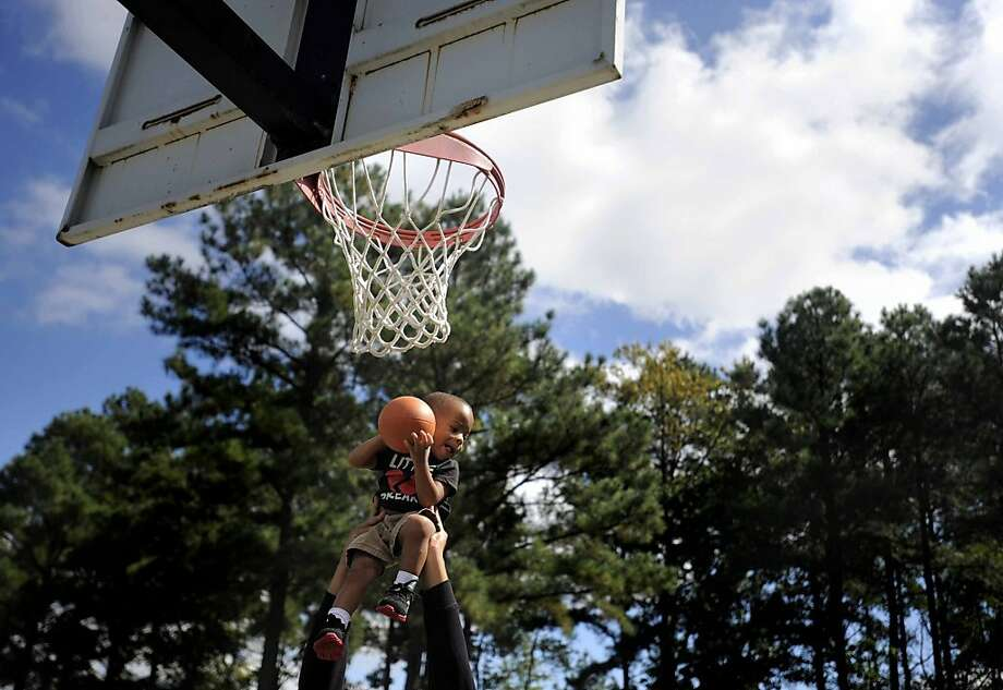 Kiddo's got game: C.J. Covington, 2, plays basketball with his cousin, Terrell James, hands pictured, while the two were hanging out with friends and family at the Dawn Community Center in Caroline County, Va. Photo: Reza A. Marvashti, Associated Press