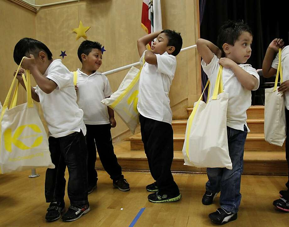 Schoolkids at Bret Harte Elementary school hoist totes stuffed with supplies at the first giveaway this school year by the nonprofit K to College organization. Photo: Brant Ward, The Chronicle