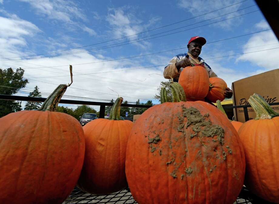 Worker Edward Tyrell  brings out pumpkins which were being displayed for sale Monday afternoon, Sept. 23, 2013, at the Golden Harvest Orchards in Valatie, N.Y. Fall began last Sunday.  (Skip Dickstein / Times Union) Photo: Skip Dickstein