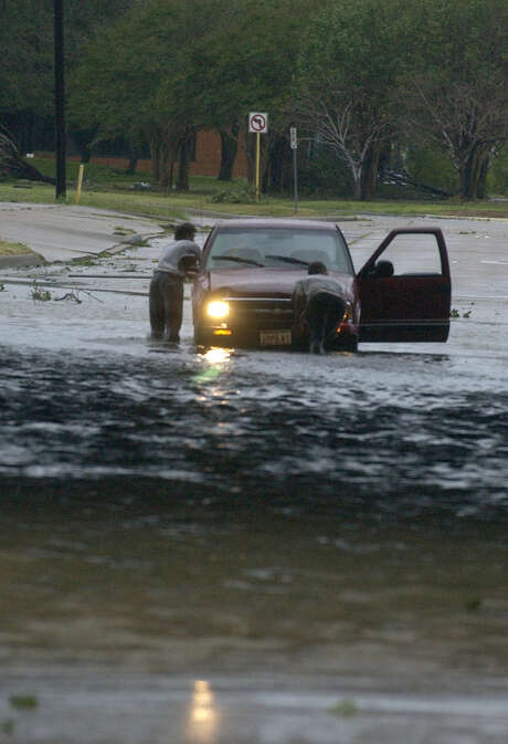 Motorists pushed their car out of high water under I-10 in Beaumont on Sept. 24, 2005, after Hurricane Rita passed through overnight.  Photo: Beaumont Enterprise / The Beaumont Enterprise