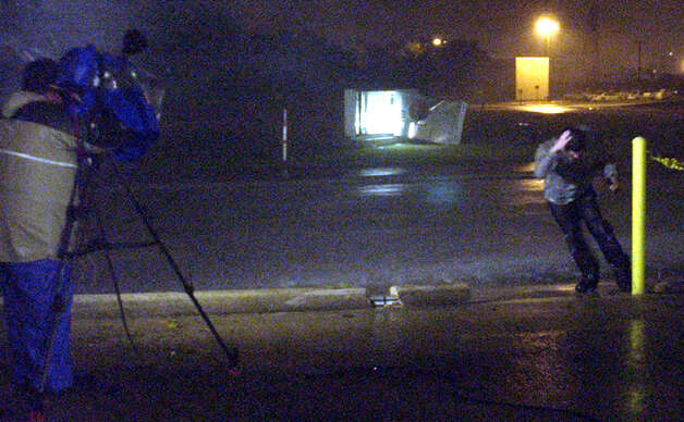 A Television reporter attempts to do a live stand up report around midnight behind the Beaumont Enterprise building as Hurricane Rita's winds blow the Entergy building sign away across the street.(AP PHOTO/BEAUMONT ENTERPRISE, D. RYAN) Photo: DAVE RYAN, MBR / THE BEAUMONT ENTERPRISE