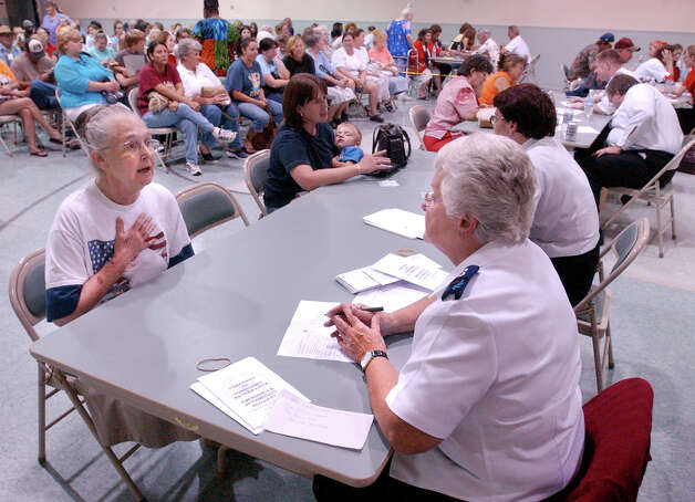 Era Puckett, 70, of Silsbee, Texas, left, speaks to Salvation Army volunteer, Margaret Peppy, 69, of Montreal, Canada, Wednesday afternoon at First Pentecostal Church in Silsbee, Texas, while applying for aid from the Salvation Army.  Hundreds from Hardin County, Texas stood in line for hours to apply for help in the aftermath of Hurricane Rita. (AP Photo/The Beaumont Enterprise,Scott Eslinger) Photo: Scott Eslinger, Staff Photographer / The Beaumont Enterprise